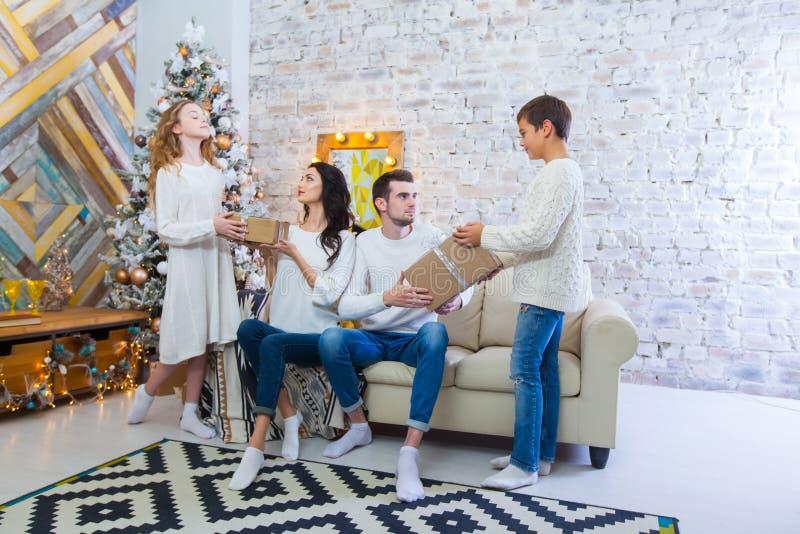 Familie die thuis vieren vader, moeder en kinderen op de achtergrond van de Kerstboom Nieuwjaar en Kerstmis royalty-vrije stock foto