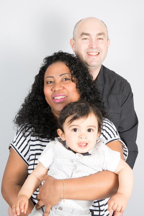 Familie die tussen verschillende rassen met Afrikaanse Amerikaanse moeder Kaukasische vader en gemengde kinderenzoon glimlachen royalty-vrije stock afbeelding