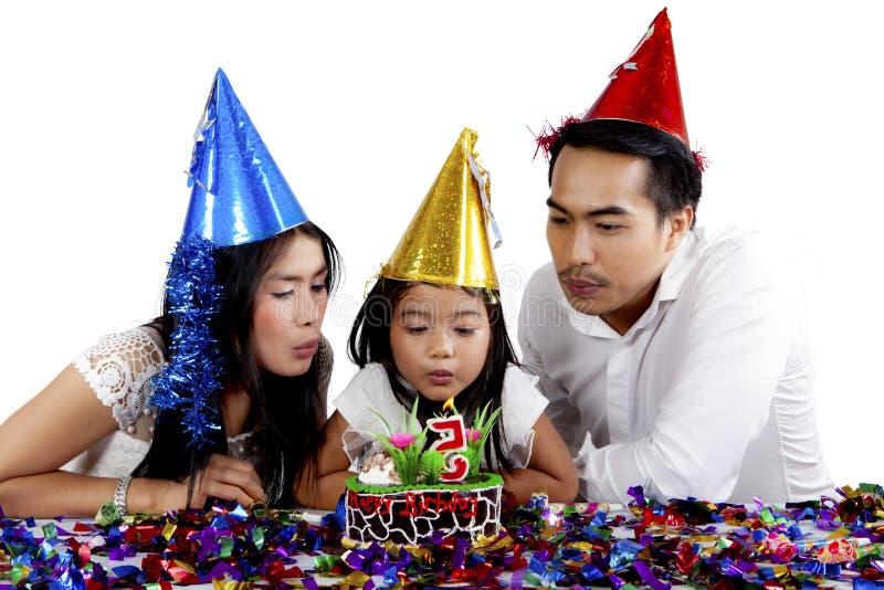 Familie die uit een kaars op de cake blazen royalty-vrije stock afbeelding