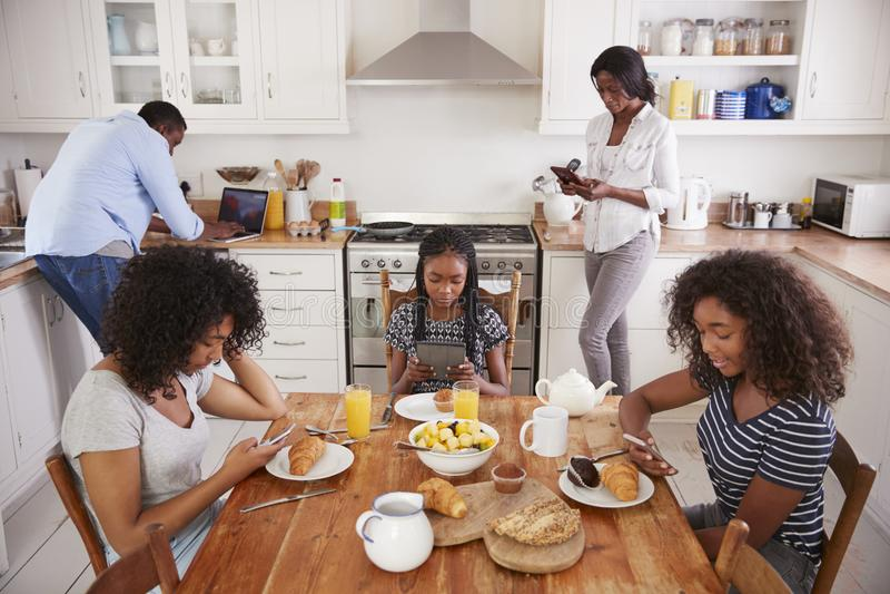 Familie, die um Frühstückstisch unter Verwendung Digital-Geräte sitzt lizenzfreie stockbilder