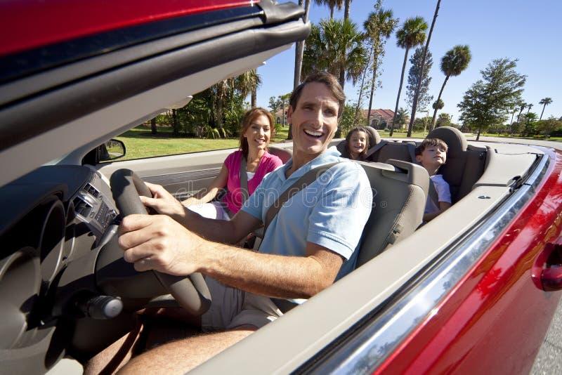 Familie, die in umwandelbares Auto antreibt stockfoto