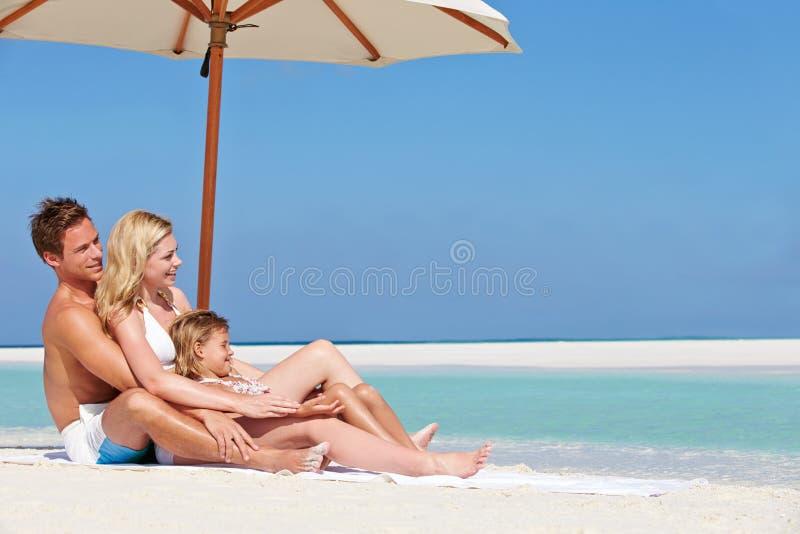 Familie, die unter Regenschirm auf Strand-Feiertag sitzt stockbilder