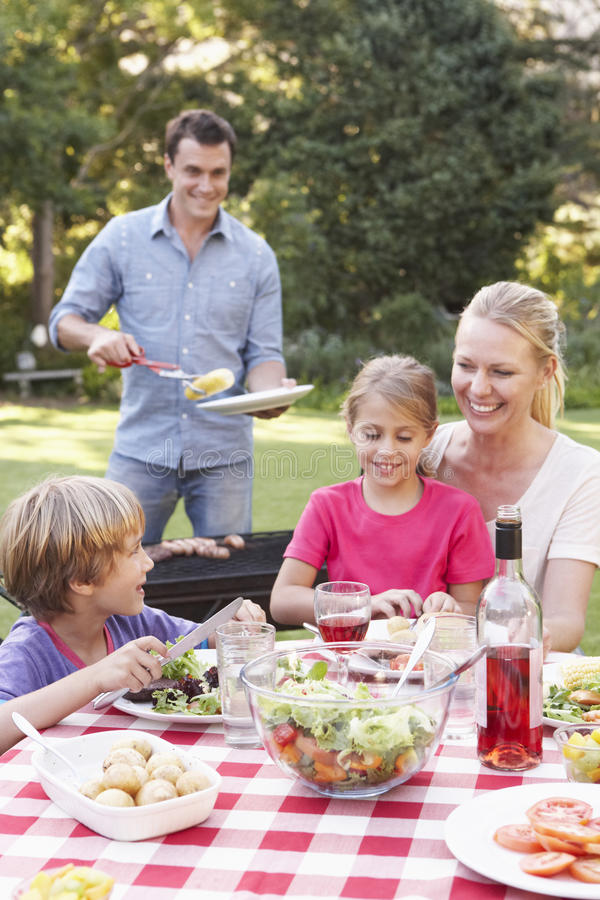 Familie die van Barbecue in Tuin samen genieten royalty-vrije stock afbeeldingen