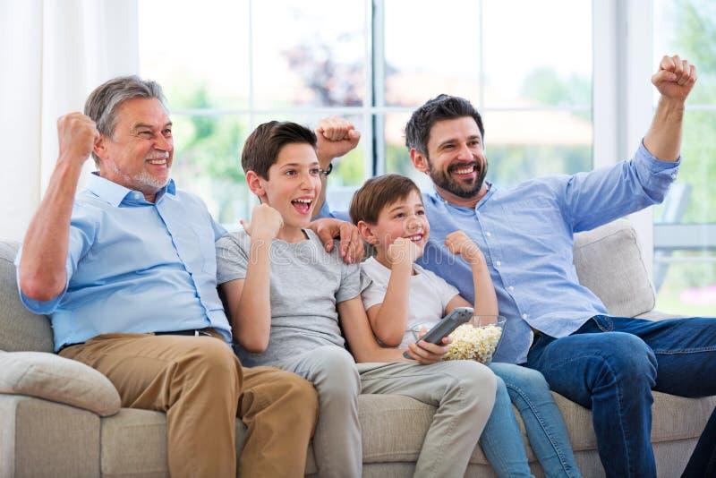 Familie die van drie generaties op TV letten stock fotografie