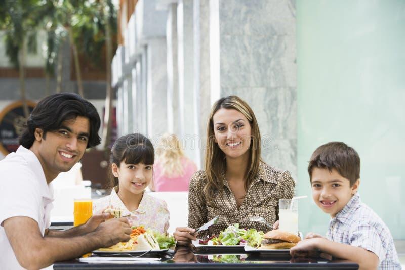 Familie die van lunch geniet bij koffie