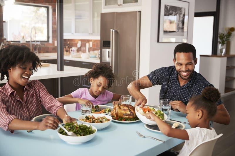 Familie die van Maaltijd thuis samen genieten rond Lijst stock foto