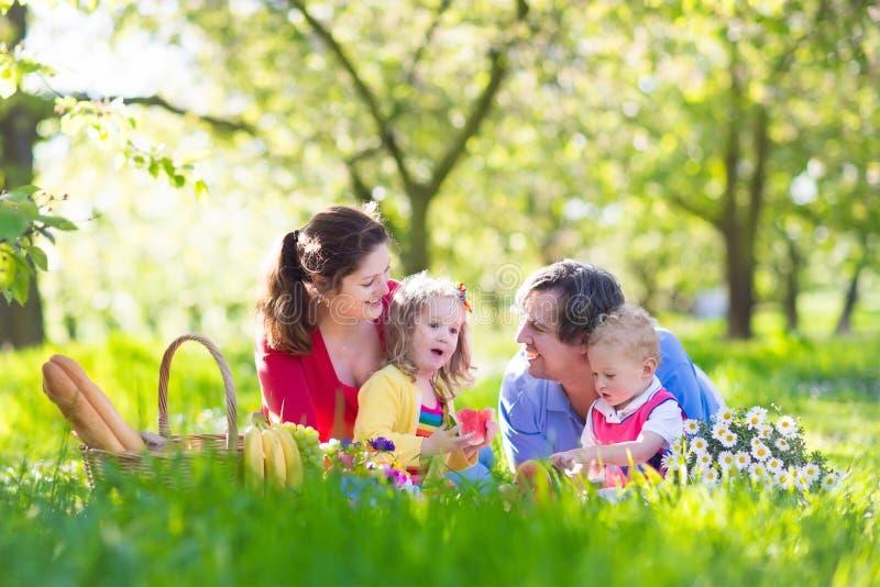 Familie die van picknick in bloeiende tuin genieten royalty-vrije stock fotografie