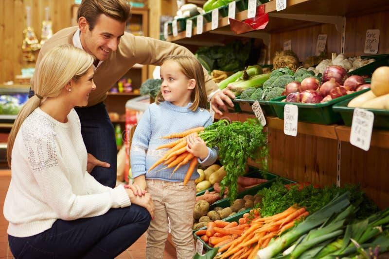 Familie die Verse Groenten in Landbouwbedrijfwinkel kiezen stock afbeelding