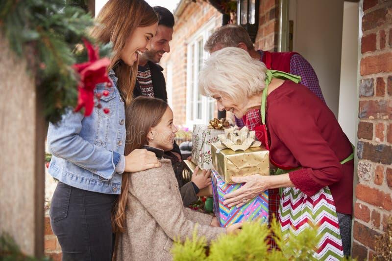 Familie, die von den Großeltern gegrüßt wird, wie sie für Besuch am Weihnachtstag mit Geschenken ankommen stockfotografie