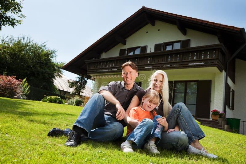 Familie, die vor ihrem Haus sitzt lizenzfreie stockfotografie