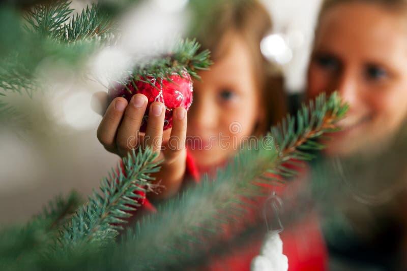 Familie, die Weihnachtsbaum verziert lizenzfreie stockfotos