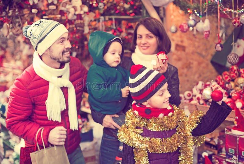 Familie, die Weihnachtsdekoration kauft lizenzfreie stockfotos