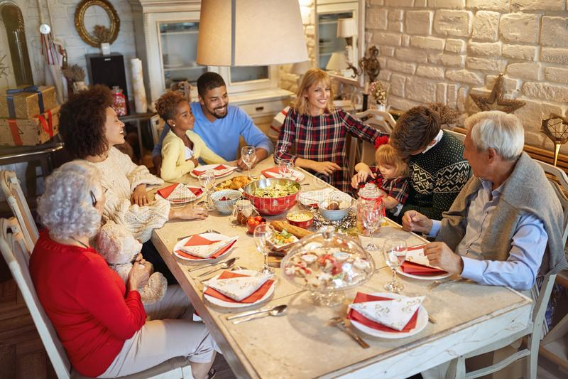 Familie, die Weihnachtszeit und Weihnachtsessen genießen feiert stockfotos