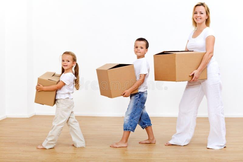 Familie die zich binnen aan een nieuw huis beweegt stock afbeeldingen