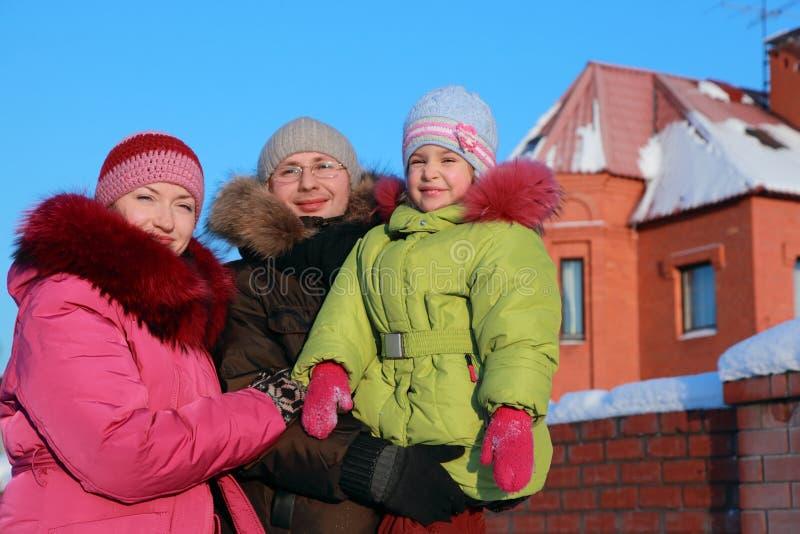Familie die zich in openlucht in de winter dichtbij huis bevindt stock foto's