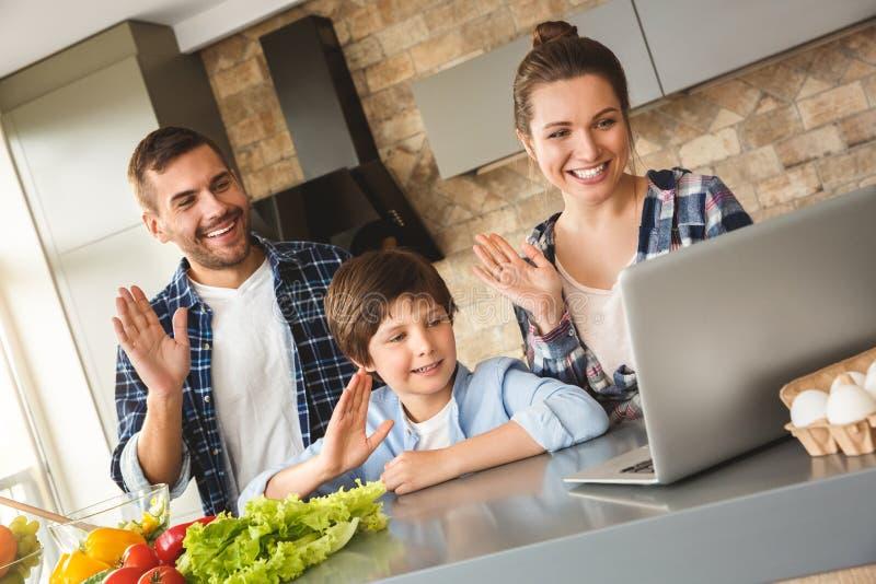 Familie die zich thuis in keuken bevinden die samen videopraatje op laptop gebruiken die aan vrolijke camera golven stock foto