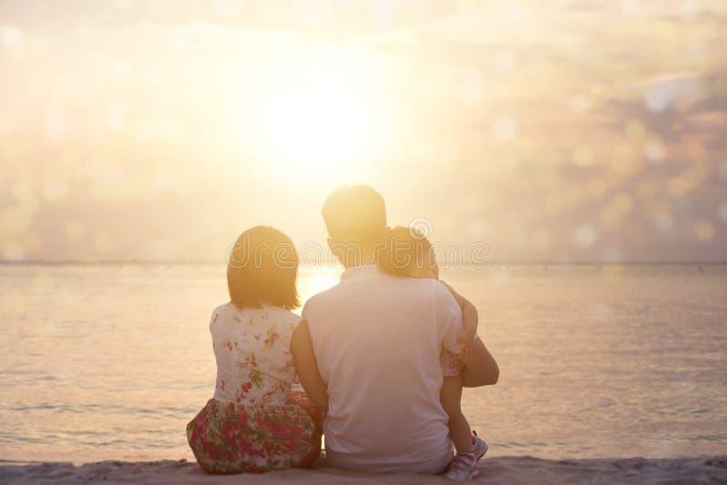 Familie die zonsondergang van mening genieten bij kust royalty-vrije stock foto