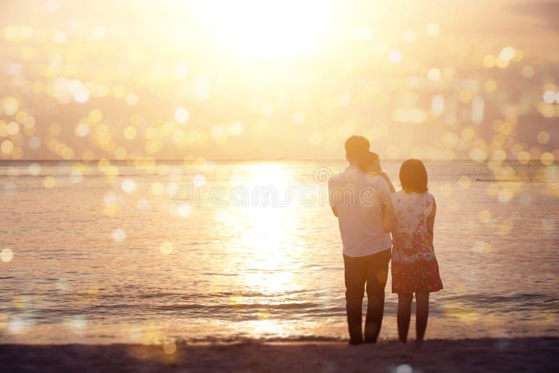 Familie die zonsondergang van mening genieten bij kustlijn stock foto's