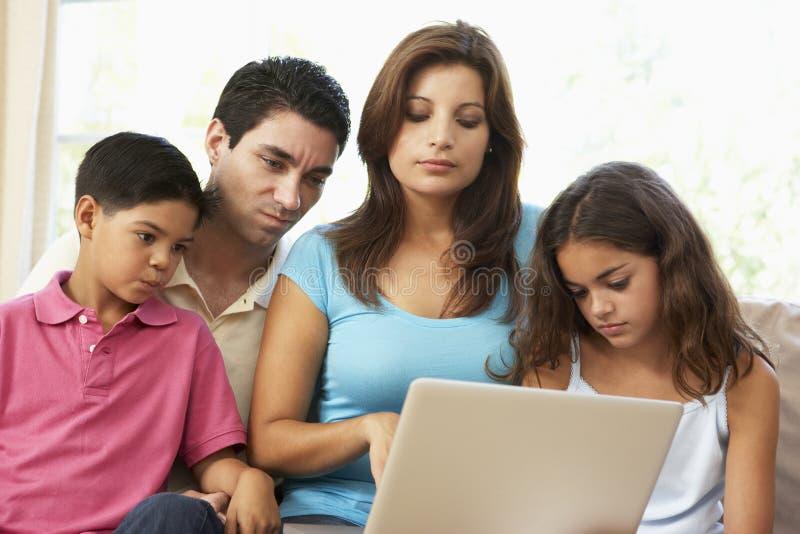 Familie, die zu Hause auf Sofa mit Laptop sitzt stockbilder