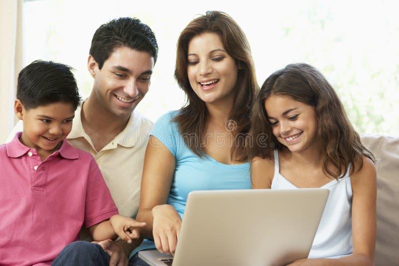 Familie, die zu Hause auf Sofa mit Laptop sitzt lizenzfreie stockbilder