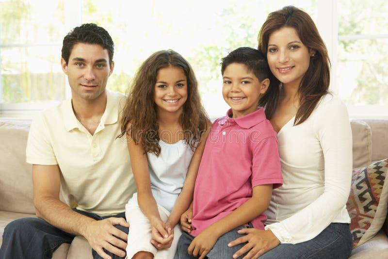 Familie, die zu Hause auf Sofa sitzt stockbild