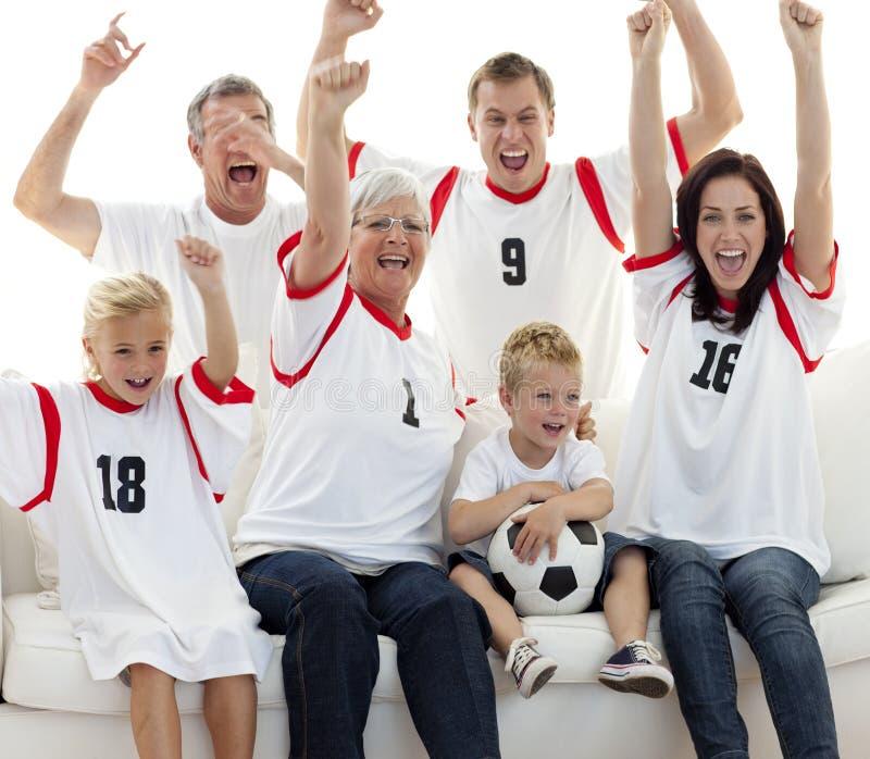Familie, die zu Hause ein Ziel feiert lizenzfreies stockbild