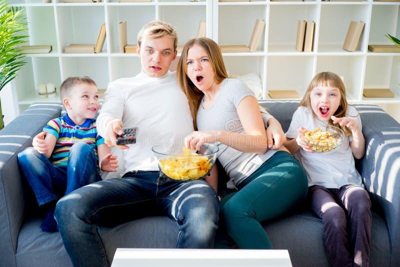 Familie, die zu Hause furchtsamen Film aufpasst lizenzfreie stockbilder