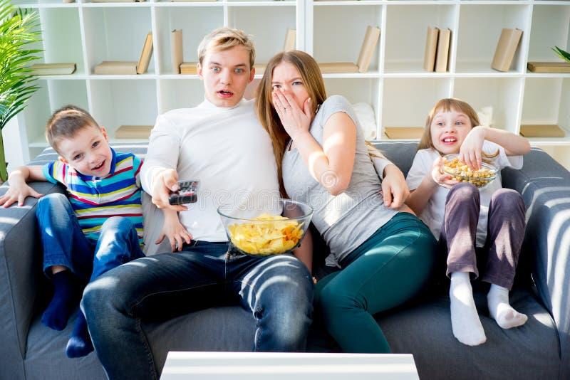 Familie, die zu Hause furchtsamen Film aufpasst stockbild