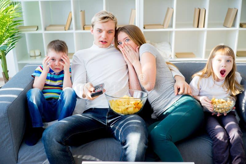 Familie, die zu Hause furchtsamen Film aufpasst lizenzfreie stockfotos