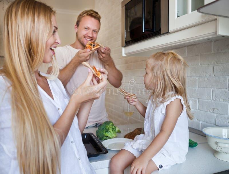 Familie, die zu Hause Pizza zusammen isst stockbild