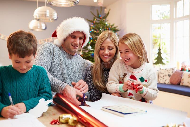 Familie, die zu Hause Weihnachtsgeschenke einwickelt lizenzfreie stockbilder