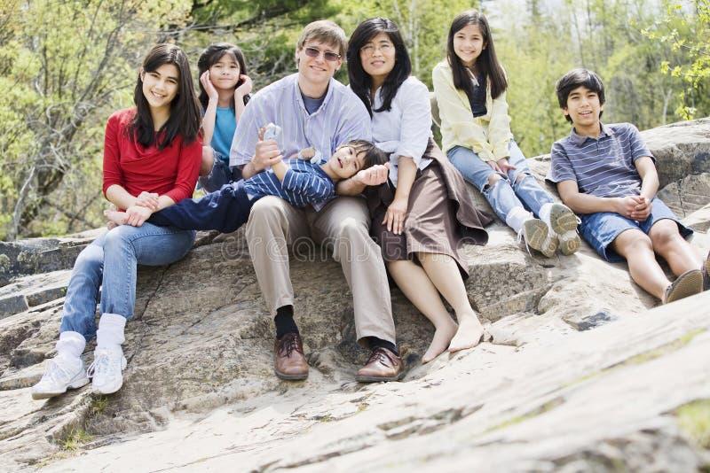 Familie, die zusammen auf felsiger Leiste sitzt stockbilder