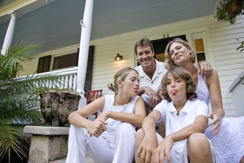 Familie, die zusammen auf Jobstepps des vorderen Portals sitzt stockfoto