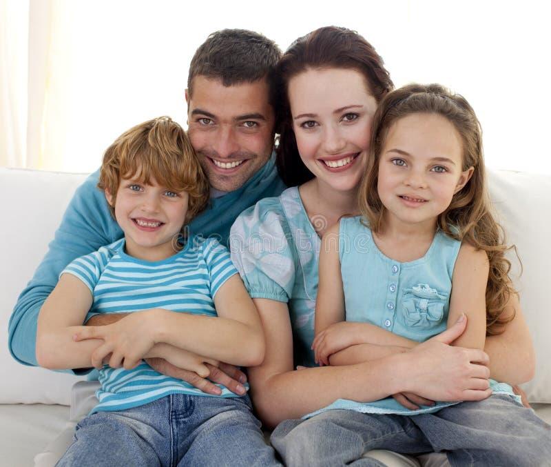 Familie, die zusammen auf Sofa sitzt stockbild