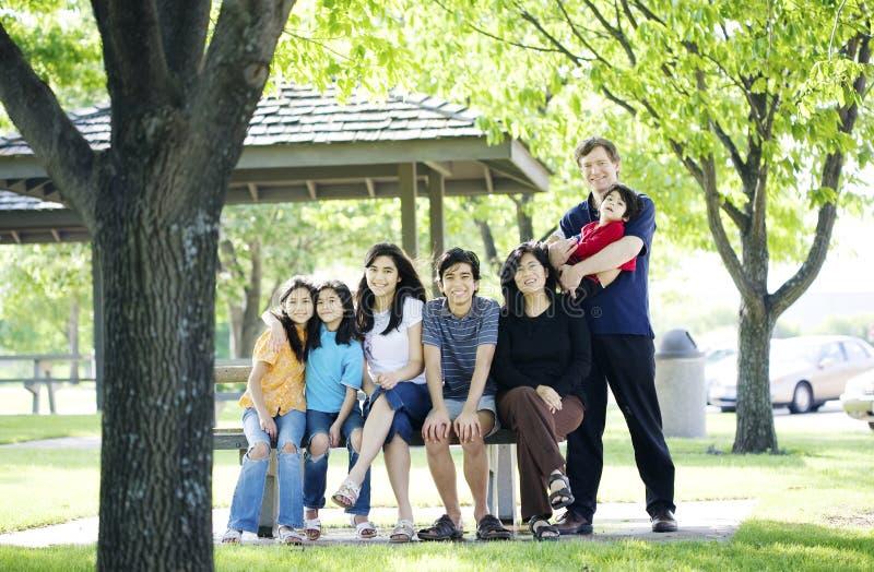 Familie, die zusammen draußen auf Picknickbank sitzt lizenzfreies stockbild