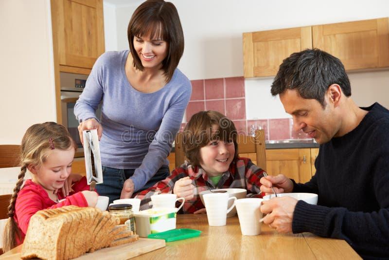 Familie, die zusammen Frühstück in der Küche isst stockfotografie