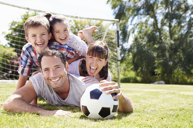 Familie, die zusammen Fußball im Garten spielt stockfotos