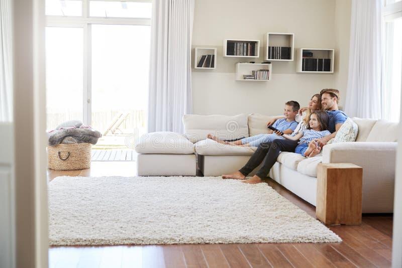 Familie, die zusammen im Sofa At Home Watching Fernsehen sitzt lizenzfreies stockfoto