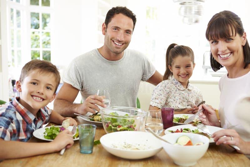 Familie, die zusammen Mahlzeit um Küchentisch isst lizenzfreie stockbilder