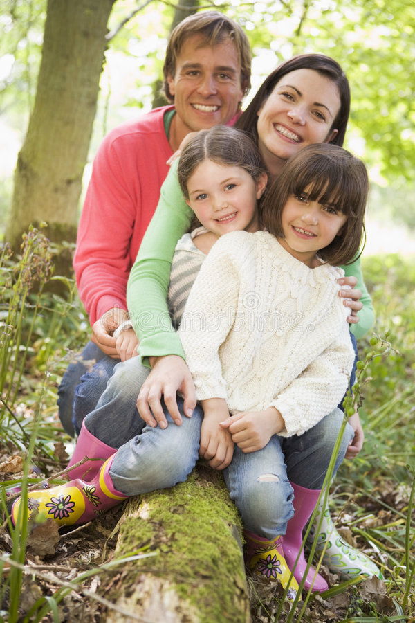 Familie draußen im Holz, das auf dem Protokolllächeln sitzt lizenzfreie stockfotos