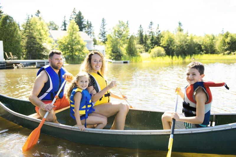 Familie in einem Kanu auf einem See, der Spaß hat stockfotos