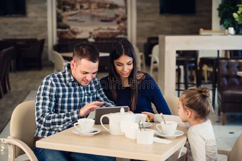 Familie, Elternschaft, Technologieleutekonzept - glückliche Mutter, Vater und kleines Mädchen mit dem Tabletten-PC-Computer, der  lizenzfreie stockfotos