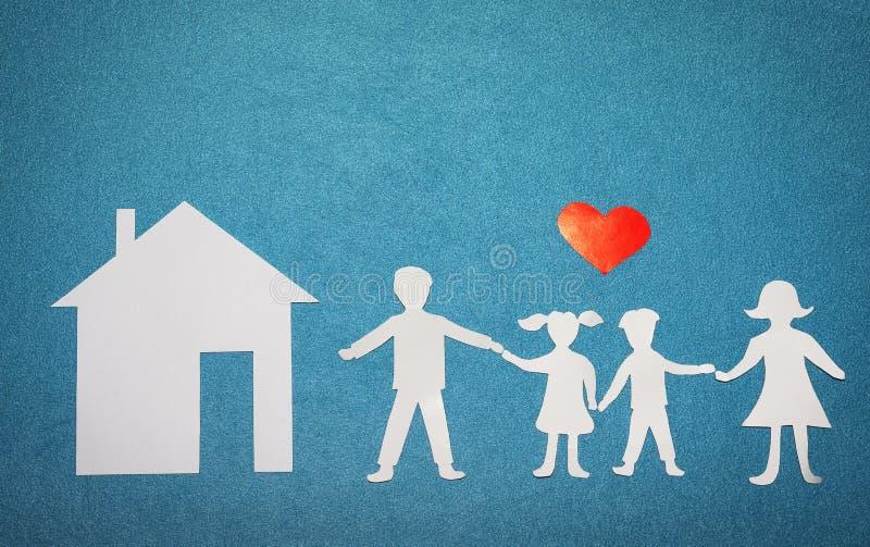 Familie en huisliefdeconcept Document huis en familie op blauwe geweven achtergrond Rood hart over familie en huissilhouetten stock afbeeldingen
