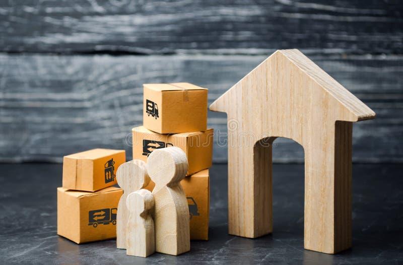 Familie en kartondozen dichtbij het huis Het concept zich het bewegen aan een nieuw huis, verhuizing Het gaan naar een ander stad stock afbeelding