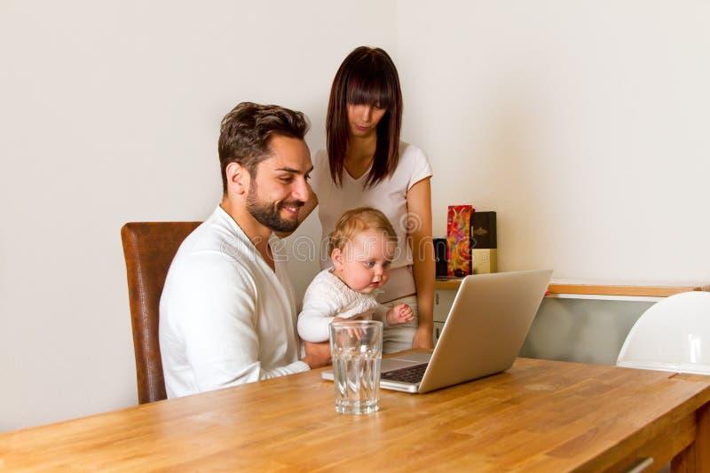 Familie en un ordenador portátil imágenes de archivo libres de regalías