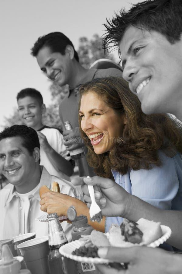 Familie en vrienden die bij barbecue genieten van stock afbeeldingen