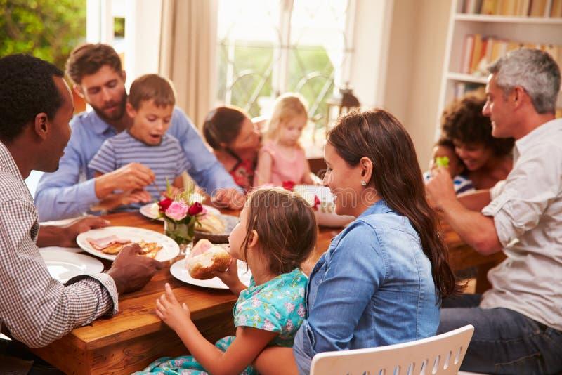 Familie en vrienden die bij een eettafel zitten royalty-vrije stock fotografie