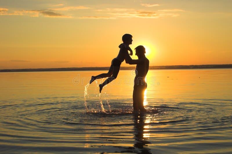 Familie en zonsondergang stock foto's