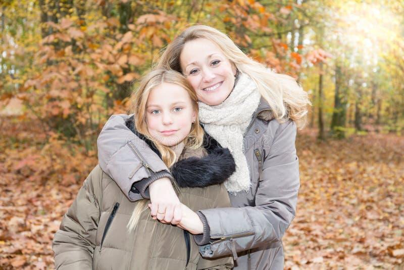 Familie enige moeder blond met mooie meisjesdochter in de herfstpark in openlucht stock afbeelding