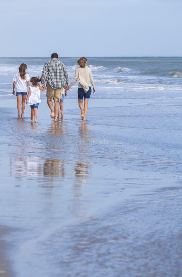 Familie erzieht die Mädchen-Kinder, die auf Strand gehen lizenzfreie stockfotografie